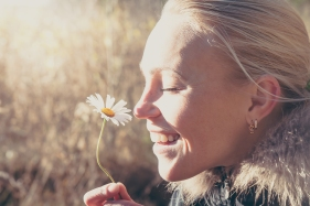 Happy woman smelling daisy flower hanging it in hands