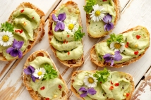 Delicious canapes with avocado paste and edible flowers on wooden background